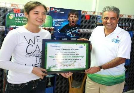 Ông Mundlay Shekhar, Tổng giám đốc Công ty PepsiCo Việt Nam, đang trao danh hiệu Cửa hàng bán lẻ vì môi trường cho chị Hoa, đại diện quán café 005 (Chung cư Sư Vạn Hạnh, TP.HCM).