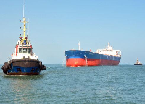 """Sau tròn một năm hạ thủy, sáng nay, Công ty công nghiệp tàu thủy Dung Quất buộc phải điều động các tàu lai dắt tàu """"Dung Quất 01"""" neo đậu suốt nhiều tháng qua từ ngoài khơi vào gần bờ để bổ sung, tu sửa nhiều hạng mục theo yêu cầu của chủ đầu tư là Tổng công ty CP Vận tải Dầu khí (PV Trans)."""