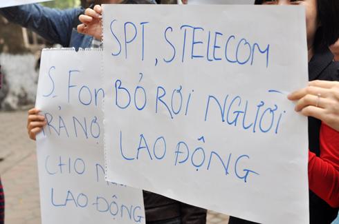 Nhân viên S-Fone căng biểu ngữ trước cổng trụ sở của công ty trên đường Trần Hưng Đạo. Ảnh: Anh Quân