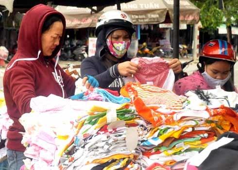 Lựa chọn quần, áo cho con trẻ trên hè phố. Trung bình mỗi ngày buôn bán quần, áo lưu động, mỗi tiểu thương thu nhập (trừ chi phí) nhiều nhất cũng khoảng 250.000 đồng.