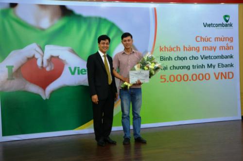 Ông Huỳnh Song Hào (bên trái), Phó giám đốc Vietcombank HCM đã trao số tiền thưởng 5 triệu đồng cho khách hàng Đoàn Minh Đức, đã tham gia bình chọn cho Vietcombank trong tuần thứ hai của chương trình My Ebank.