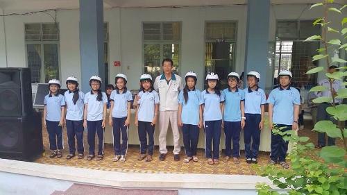 Đại diện công ty tặng mũ bảo hiểm cho học sinh