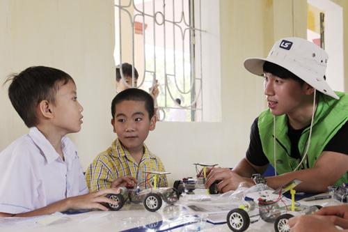 sinh viên tình nguyện viên đang làm mô hình xe oto mặt trời với trẻ em Dream School