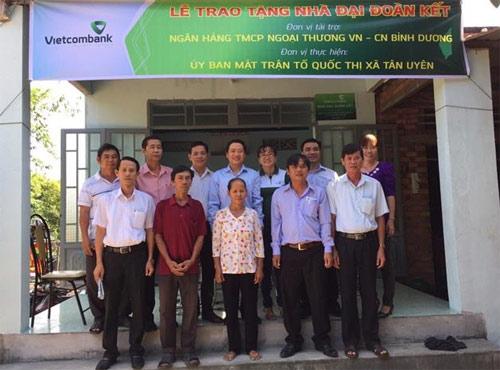 Ông Nguyễn Khánh Thắng - Phó giám đốc Vietcombank Bình Dương (hàng sau, thứ tư từ trái sang) trao Quyết định tặng nhà đại đoàn kết cho hộ ông Phạm Văn Công