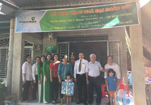 Ông Nguyễn Khánh Thắng- Phó Giám đốc Vietcombank Bình Dương (thứ tư từ phải sang) trao Quyết định tặng nhà đại đoàn kết cho hộ bà Phạm Thị Dương