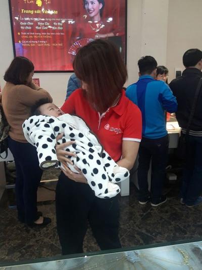 Em bé 8 tháng theo mẹ đi mua vàng ngày Thần Tài tại Trung tâm DOJI được nhân viên bán hàng hỗ trợ bế đỡ