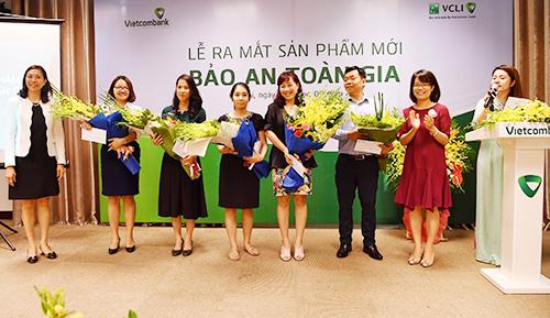 Bà Đoàn Hồng Nhung (thứ 2 từ phải sang) và bà Young Lai Yin (ngoài cùng bên trái) tặng hoa chúc mừng các khách hàng tham gia sản phẩm Bảo An Toàn Gia