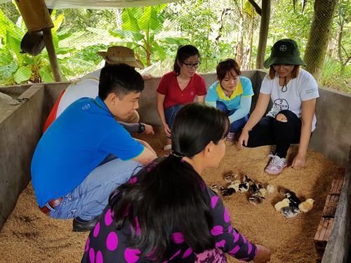 Bà Đặng Thị Mành được các tình nguyện viên Bayer Việt Nam hướng dẫn kỹ thuật nuôi gà bằng đệm lót sinh học