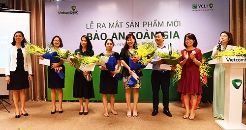 Bà Đoàn Hồng Nhung  Trưởng phòng Quản lý Bán sản phẩm bán lẻ, Thành viên Hội đồng thành viên Công ty VCLI (Thứ 2 từ phải sang) và bà Young Lai Yin  Tổng Giám đốc VCLI (ngoài cùng bên trái) tặng hoa chúc mừng các khách hàng tham gia sản phẩm Bảo An Toàn Gia