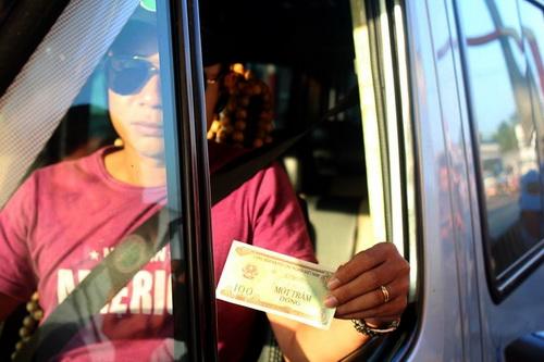 Tài xế nhận tiền thối 100 đồng tại trạm BOT. Ảnh: Thái Hà.