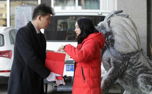 Khách hàng kiểm tra món hàng hiệu mà cô mua qua mạng, được giao bằng dịch vụ VIP. Ảnh: Reuters.