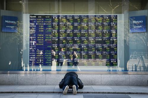 Phản ứng của một người Nhật khi nhìn bảng điện tử chứng khoán sáng nay. Ảnh: Bloomberg