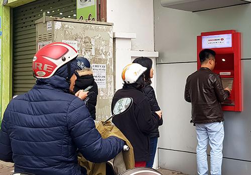 Sáng 11/2, nhiều người dân xếp hàng rút tiền trước các trụ ATM dịp cận Tết Nguyên đán 2018. Ảnh: HT