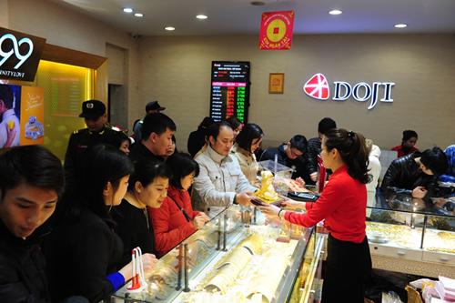 Cảnh nhộn nhịp mua vàng ngày vía Thần Tài tại trung tâm Đống Đa, 209 Xã Đàn, Hà Nội. Sản phẩm mỹ nghệ mạ vàng Nano hình Tuất có tác dụng hóa giải sát khí, đón bình an có mức giá từ 1 đến chục triệu đồng, được nhiều khách hàng lựa chọn