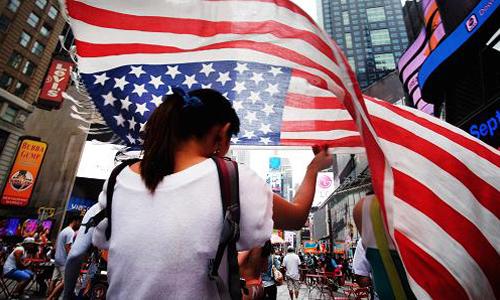 Một cô gái cầm quốc kỳ trên quảng trường Times, New York. Ảnh: AFP.