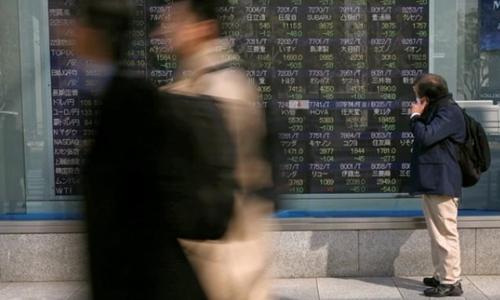 Một người đàn ông nhìn bảng điện tử giá cổ phiếu tại Tokyo. Ảnh: Reuters