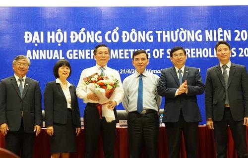 Ông Phạm Quang Tùng (người cầm hoa) và ban lãnh đạo BIDV. Ảnh: Minh Sơn