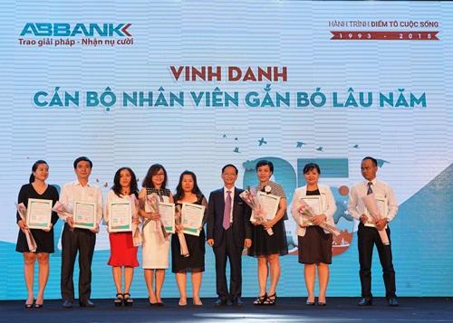 Ông Vũ Văn Tiền - Phó Chủ tịch HĐQT ABBank tặng hoa và giấy khen cho cán bộ, nhân viên gắn bó lâu năm với Ngân hàng An Bình.