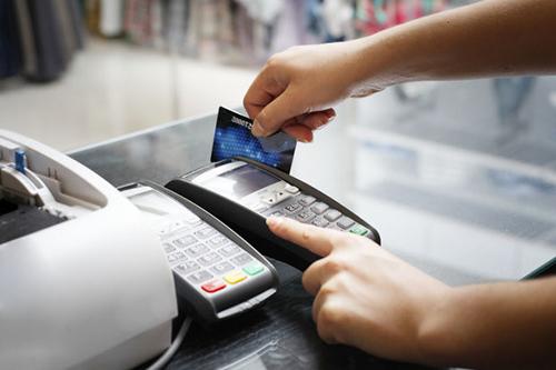Thanh toán thẻ ngân hàng qua máy POS tại một điểm mua hàng.