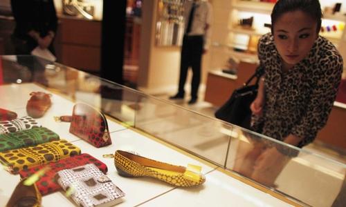 Một phụ nữ chọn đồ tại trung tâm thương mại ở Thượng Hải. Ảnh: Reuters