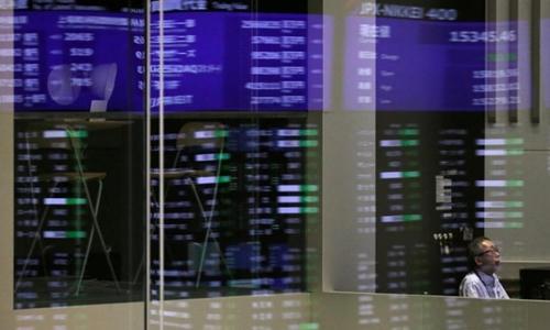 Các chỉ số phản chiếu trên một cửa kính tại Sàn giao dịch Tokyo. Ảnh: Reuters