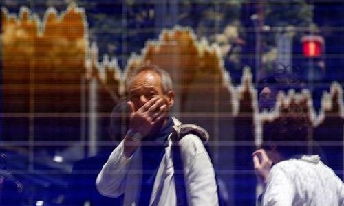 Một người đàn ông nhìn bảng điện tử trên đường phố Tokyo. Ảnh: Reuters