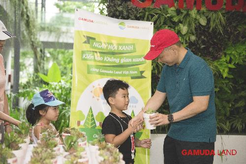 Đại diện Gamuda Land Việt Nam - ông Dennis Ng Teck Yow - tặng chậu cây xanh cho các cư dân nhí tham gia Ngày hội Xanh.