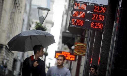 Người dân đi qua một quầy đổi tiền ở thủ đô Buenos Aires. Ảnh:AP