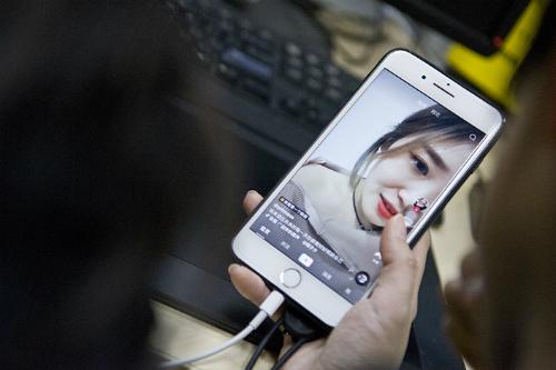 Một người dùng Trung Quốc đang xem video trên Tik Tok. Ảnh: Caixin