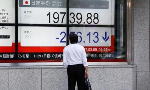 Một người đàn ông nhìn bảng điện tử bên ngoài công ty chứng khoán ở Tokyo. Ảnh: Reuters