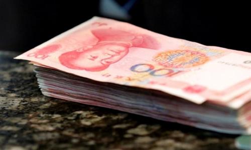 Các tờ 100 NDT trên quầy giao dịch tại một ngân hàng ở Bắc Kinh. Ảnh: Reuters