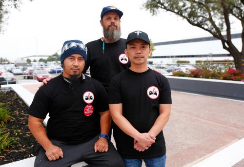 Mikey Catura ngồi bên trái và Hai Nguyen đứng cạnh bên phải chụp trước nhà máy Tesla tạiFremont, California vào tháng 8/2017. Ảnh:The Mercury News