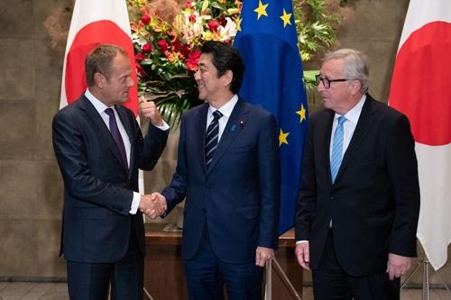 Ông Donald Tusk (trái) cùng ông Shinzo Abe và Jean-Claude Juncker. Ảnh: Bloomberg