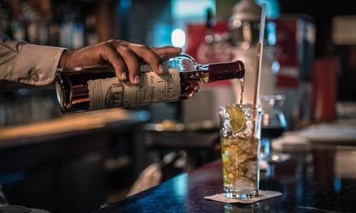 Một nhân viên pha chế đang làm cocktail với rượu rum tại Venezuela. Ảnh: Bloomberg