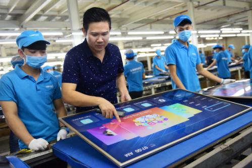 Chủ tịch Asanzo Phạm Văn Tam (phải) trực tiếp kiểm tra sản phẩm trong dây chuyền lắp ráp TV của hãng tại TP HCM.