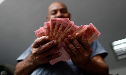 Một nhân viên đang đếm tiền tại một bãi giữ xe ở Caracas (Venezuela). Ảnh: Reuters
