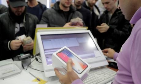 Một nhân viên đang bán iPhone X cho khách hàng tại Moscow. Ảnh: Reuters