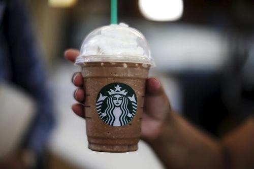 Khách hàng dùng cà phê của Starbucks trong một sân bay ở California (Mỹ). Ảnh: Reuters