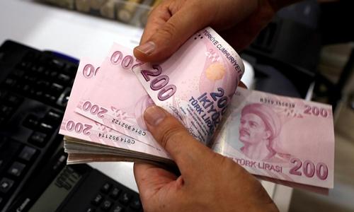 Nhân viên kiểm tiền tại một quầy đổi ngoại tệ ở Istanbul. Ảnh: Reuters