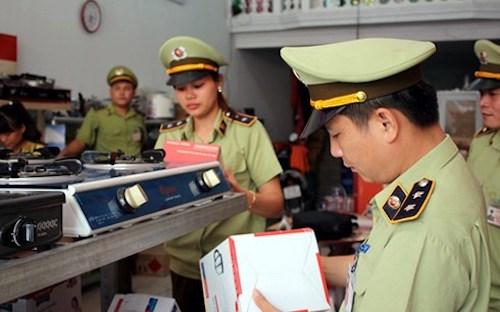Cán bộ quản lý thị trường kiểm tra hàng hoá vi phạm tại một cửa hàng kinh doanh gas. Ảnh: QLTT