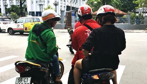 Tài xế mặc áo Mai Linh Bike đội nón Vato hỏi thăm đường tài xế Go-Viet tại TP HCM. Ảnh: Viễn Thông