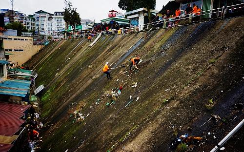Các thành viên Ờ Phượt sử dụng dây thừng để tiếp cận và thu gom rác ở bức tường dốc cạnh chợ Đà Lạt cuối tuần qua.