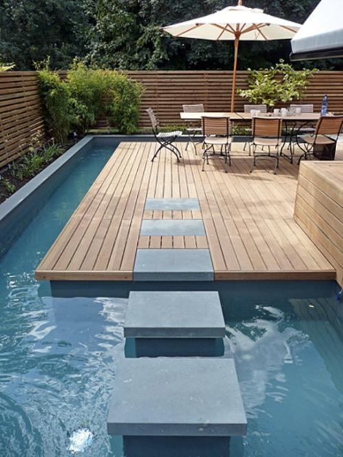 Bể bơi hình chữ U bao quanh khoảng sân sau nhà.