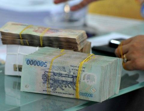 Giao dịch tiền đồng tại một ngân hàng thương mại. Ảnh: PV.