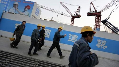 Công nhân Trung Quốc bên ngoài một công trình ở Bắc Kinh. Ảnh: Reuters