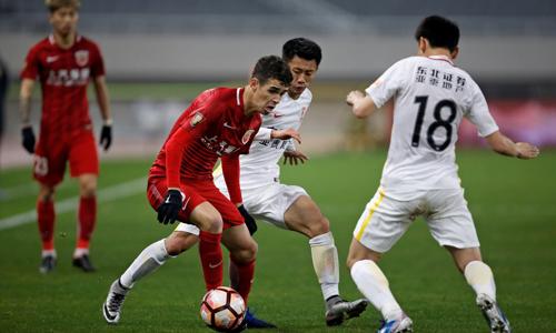 Một trận đấu của Guangzhow Evergrande (áo đỏ) - đội bóng Trung Quốc đã chi hàng chục triệu USD để chiêu mộ các ngôi sao từ châu Âu. Ảnh: Reuters