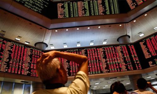 Nhà đầu tư xem bảng điện tử đỏ rực trong phiên giao dịch. Ảnh: AP