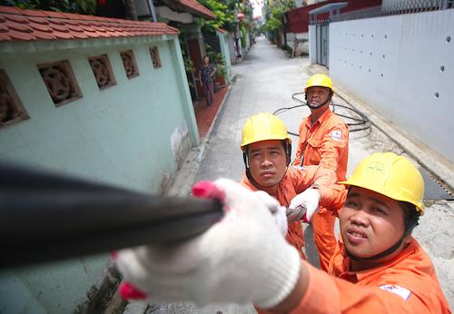 Công nhân ngành điện kéo cáp điện đến nhà khách hàng. Ảnh: Ngọc Thành