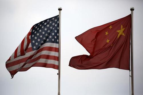 Cờ của Mỹ và Trung Quốc được treo bên ngoài một tòa nhà ở Thượng Hải (Trung Quốc). Ảnh: Bloomberg.