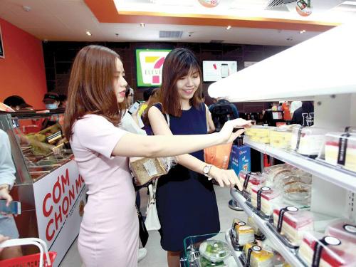 Người tiêu dùng chọn mua hàng tại cửa hàng tiện lợi. Ảnh: AP
